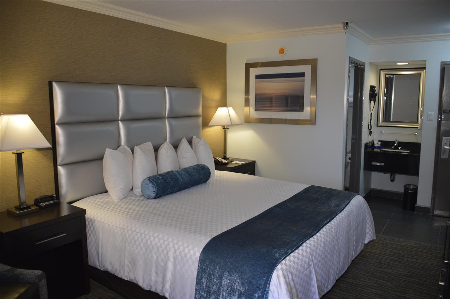 Guest Room With A King Bed Desk Microwave Refrigerator Coffee Maker Ironing Board Iron And Lounge Chair